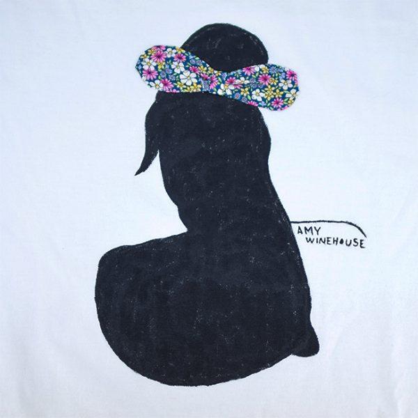 Camiseta branca de algodón, con debuxo de Amy Winehouse pintado a man con lazo de tea en azul, rosa, branco, amarelo, lila e verde