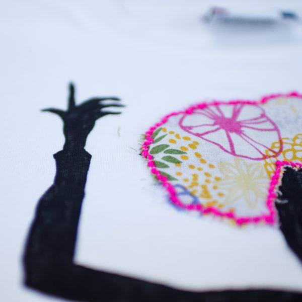 Camiseta branca de algodón, con debuxo de Celia Cruz pintado a man con turbante de tea de flores en fucsia, verde e amarelo e bordado en fucsia