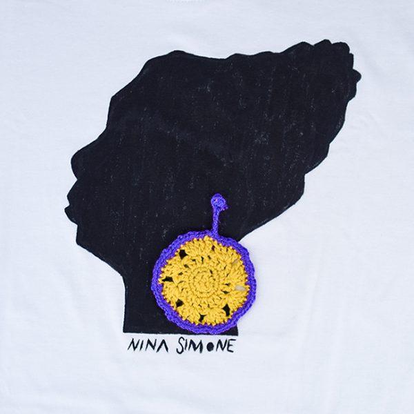 Camiseta branca de algodón, con debuxo de Nina Simone pintado a man con pendente a ganchillo en amarelo e morado