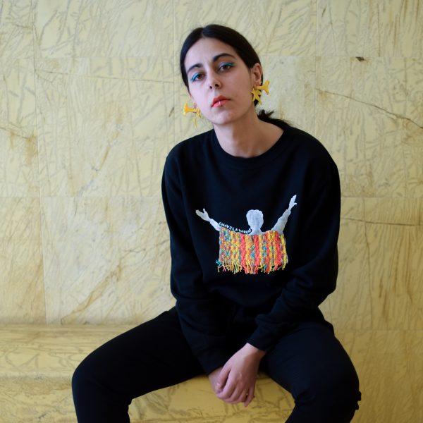 Unha modelo posa cun suadoiro negro con debuxo de Chavela Vargas pintado a man con poncho texido en coral, turquesa e amarelo